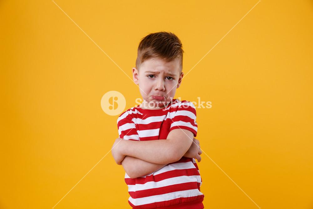 Portrait of a sad upset little boy crying isolated over orange background