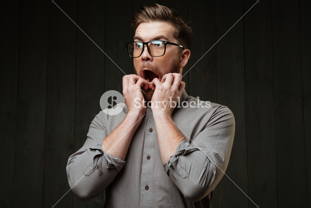 Portrait of a scared bearded man in eyeglasses looking away isolated on the black wooden background