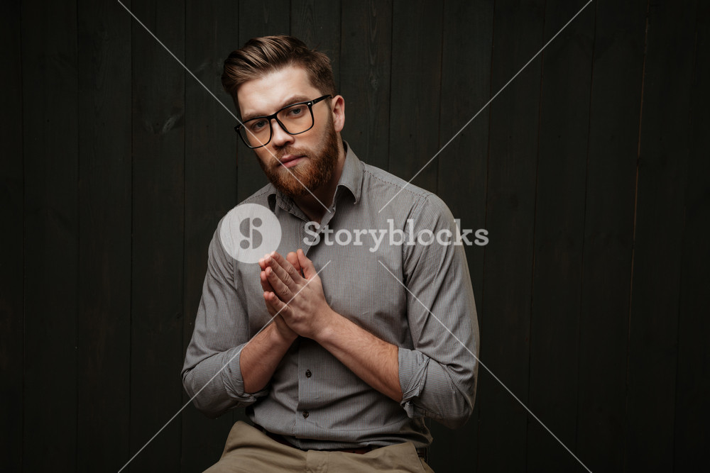 Portrait of a young bearded man in eyeglasses sitting and praying isolated on a black wooden background