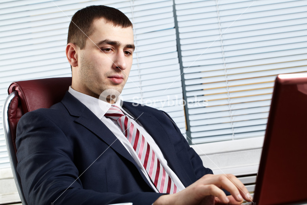 Portrait of handsome businessman sitting at table and working at computer