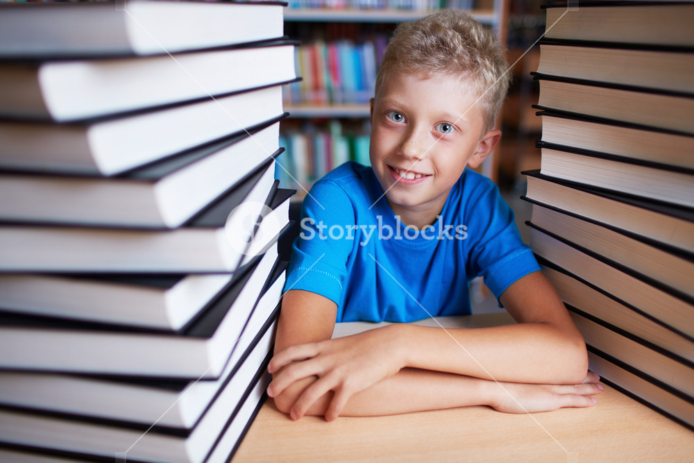 Portrait of happy schoolkid looking at camera surrounded by stacks of books