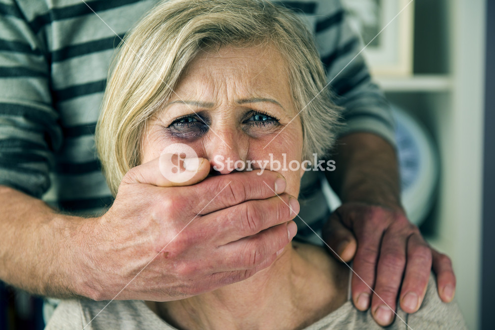 Portrait of woman victim of domestic violence. Man abusing senior woman with black eye-