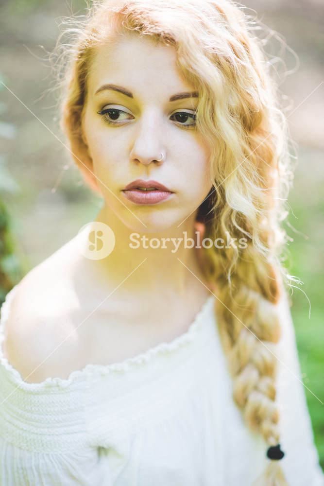 Portrait of young beautiful caucasian blonde hair woman outdoor in a city park, overlooking serene - beauty, hair care, skin care concept