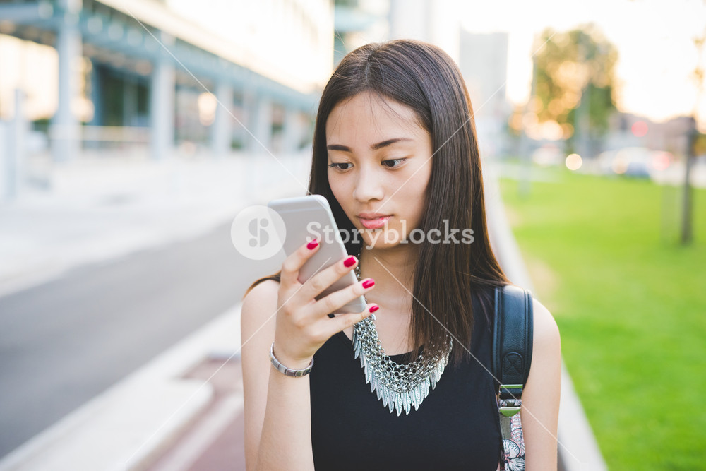Portrait of young handsome asiatic long brown straight hair woman walking outdoor in the city, looking downward and tapping the screen - technology, social network, communication concept