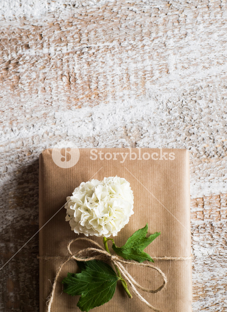 Present wrapped in brown paper decorated by lilac flower. Studio shot on white wooden background. Copy space.