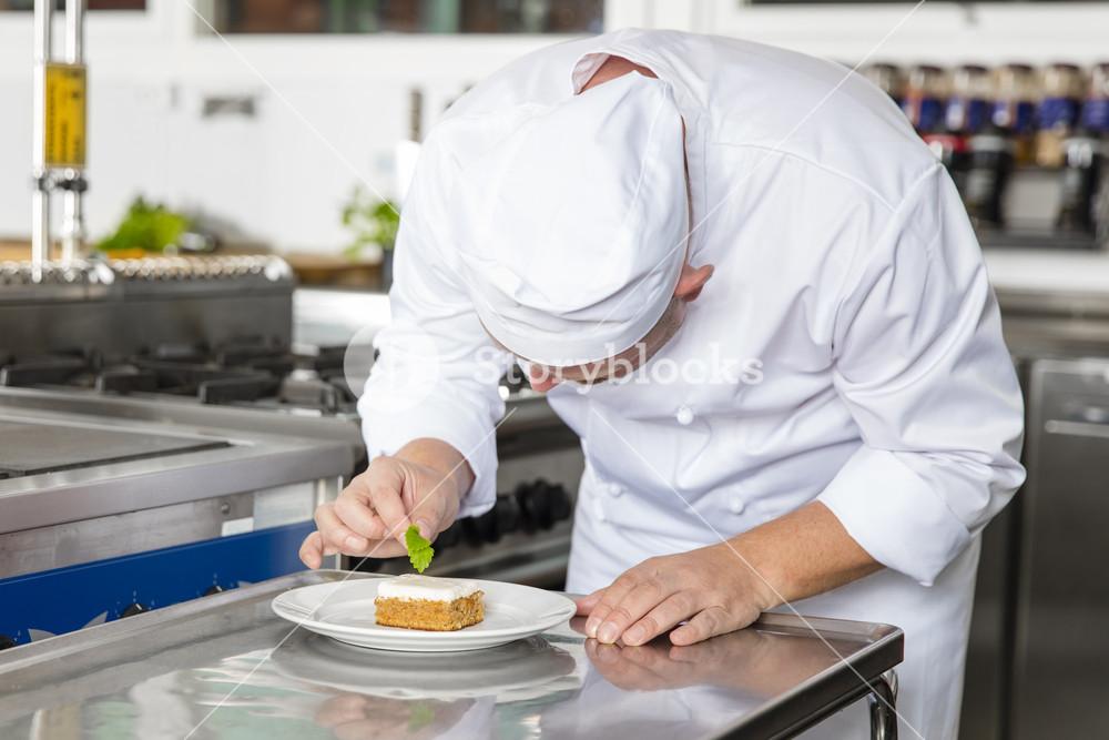 Professional chef decorate dessert cake with lemon leaf