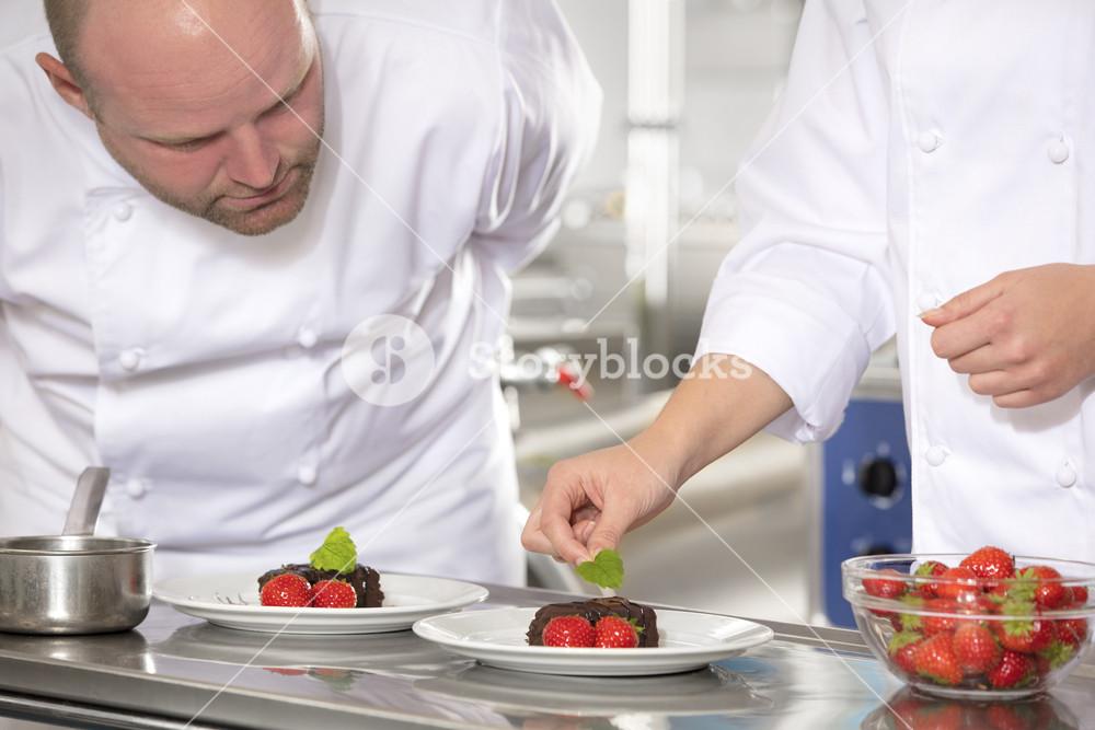 Professional chefs decorate dessert cake with lemon leaf
