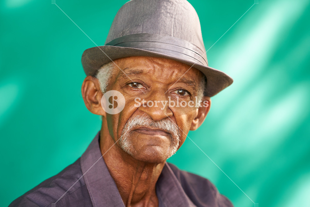Real Cuban people and feelings, portrait of sad senior hispanic man looking at camera. Worried old latino grandfather with mustache and hat from Havana, Cuba