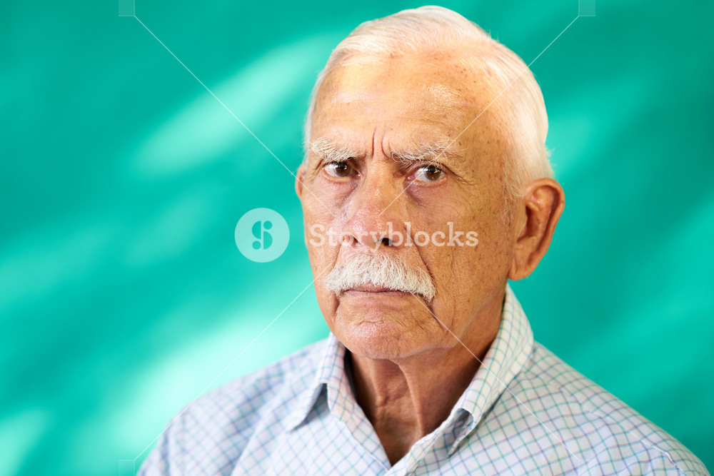Real Cuban people and feelings, portrait of sad senior hispanic man looking at camera. Worried old latino grandfather with mustache from Havana, Cuba