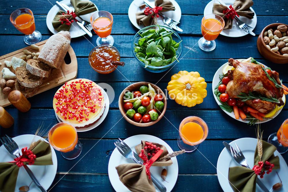 Roasted turkey, glasses with juice, vegetables, nuts, dessert, fresh bread and tableware on dinner table