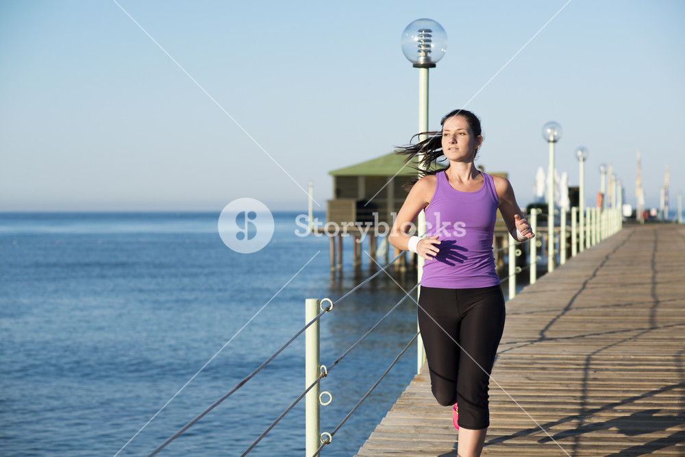 Running woman. Female runner jogging during outdoor workout on beach.