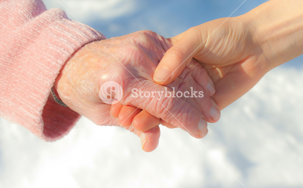 Senior and young holding hands outside over snow background