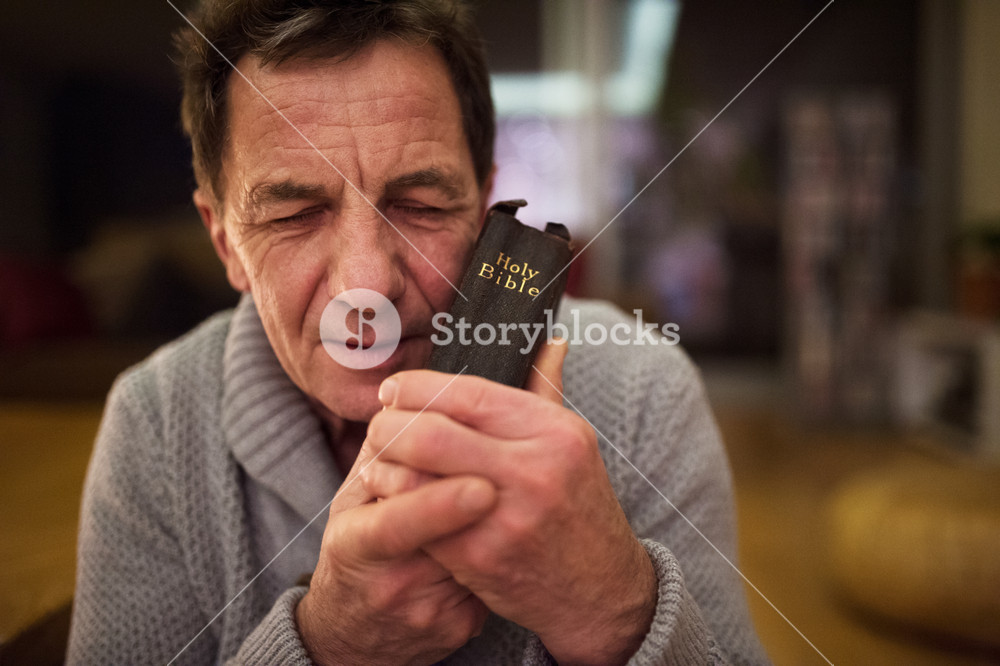 Senior man praying, holding an old Bible in his hands, eyes closed, close up.