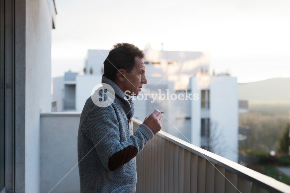 Serious senior man standing on balcony and smoking a cigarette