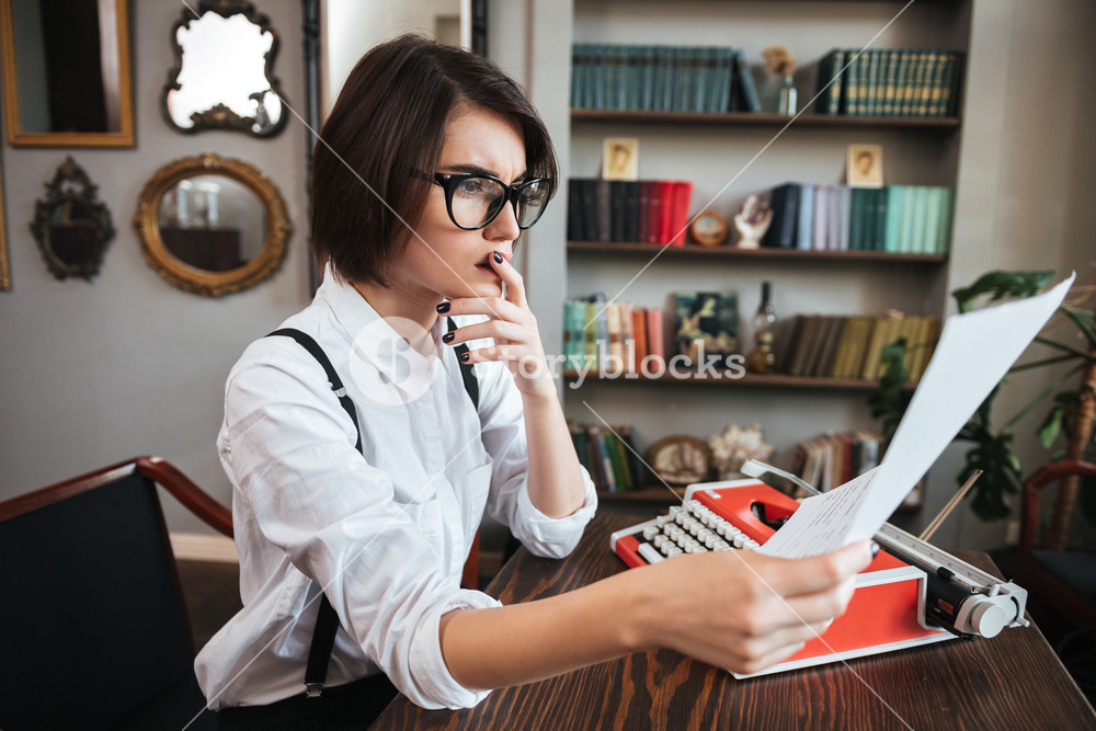 Side view of thoughtful authoress in glasses and white shirt sitting by the table with paper and typewriter