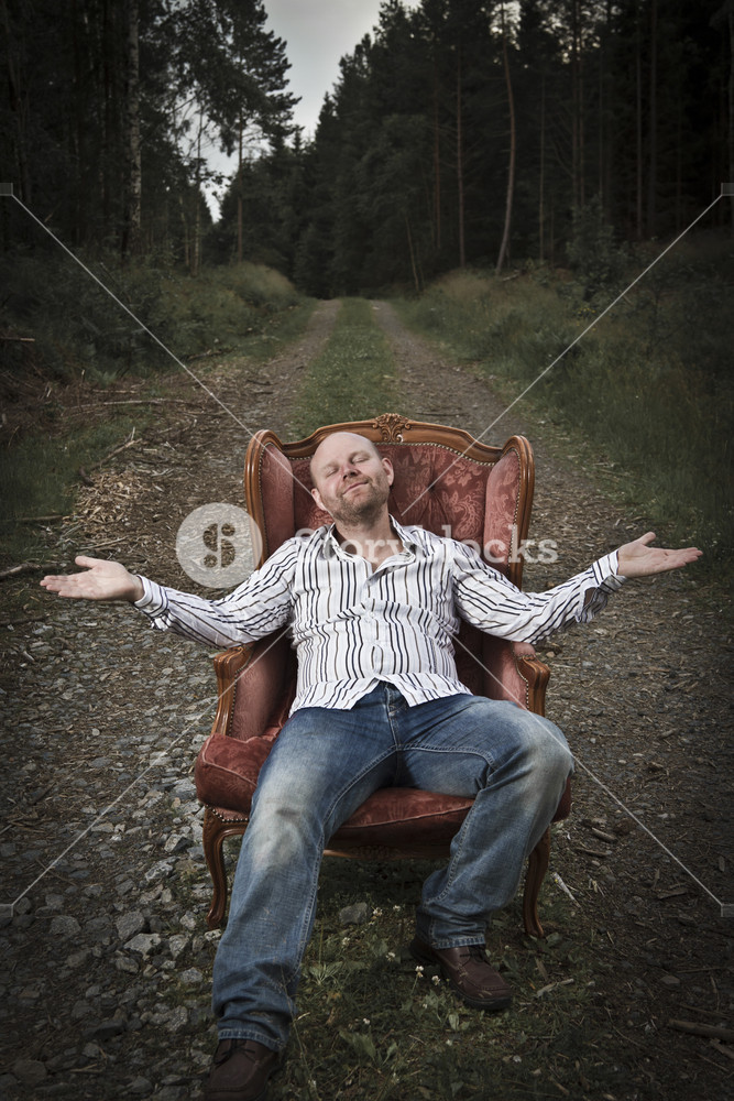 Sleazy man in a classic vintage chair in the middle of a road in the woods. Smoking cigar and get served Cognac from a woman.