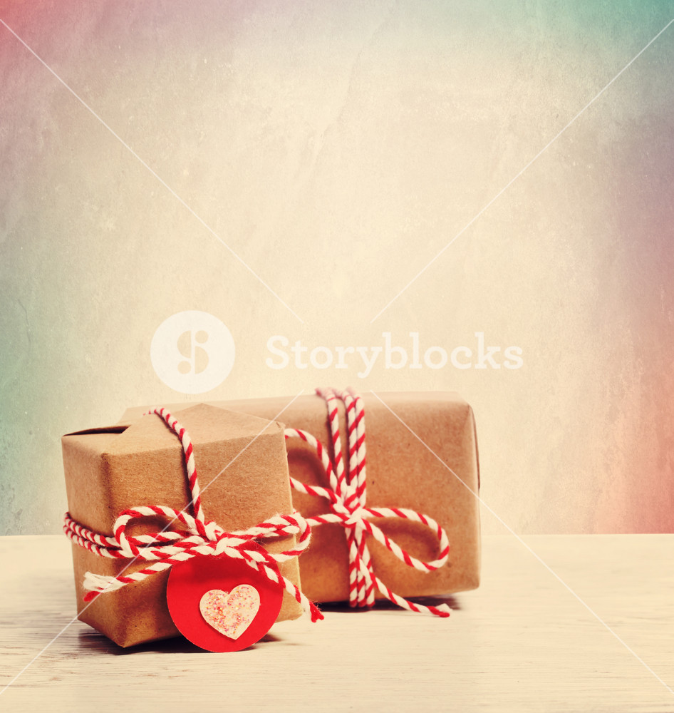 Small handmade gift boxes with heart shaped tags in pastel background