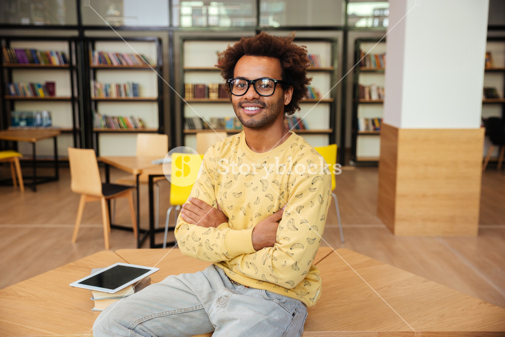 Smiling african young man in glasses sitting with arms crossed in library