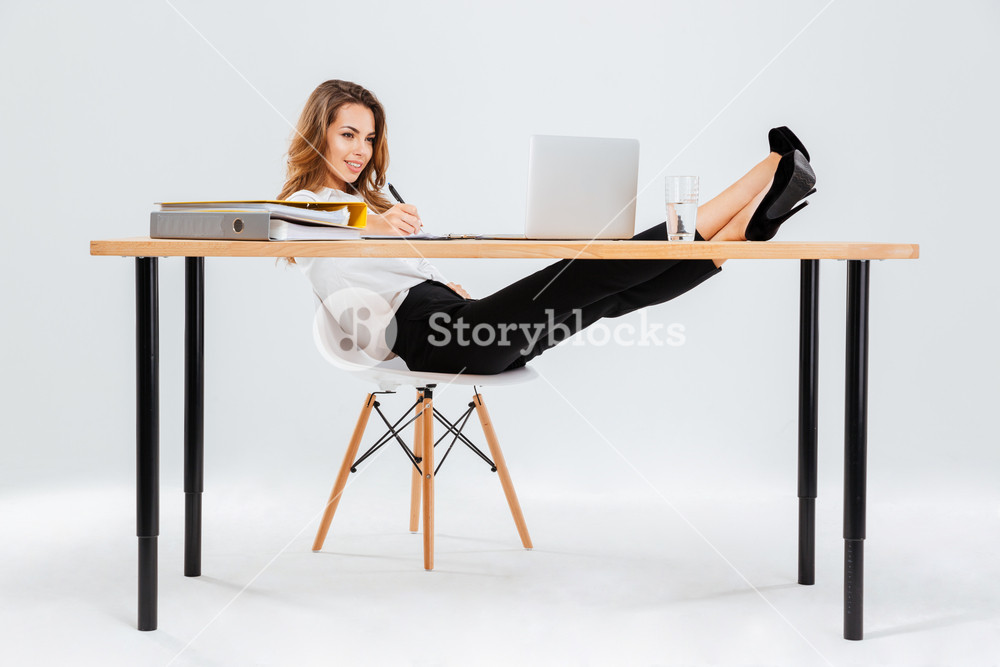 Smiling young businesswoman using laptop and writing with legs on table over white background