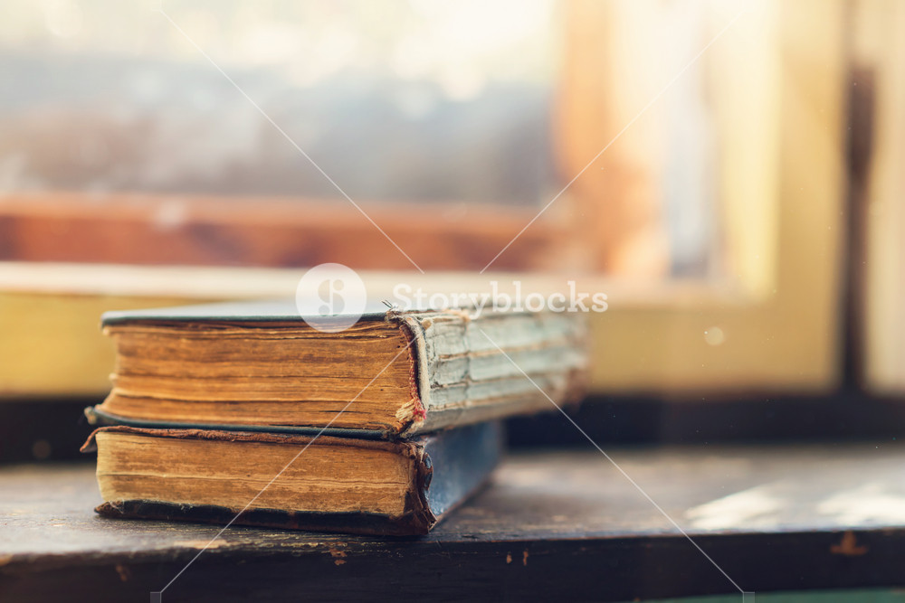 Stack of old books laid on windowsill