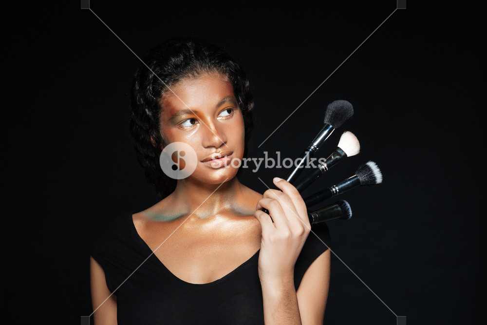 Thoughtful lovely african american young woman with makeup brushes