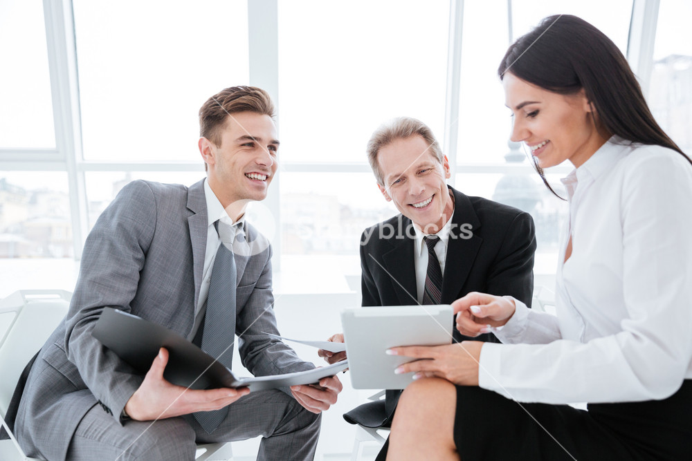 Three business people sit with tablet computer in conference room
