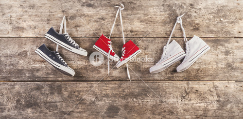Three pairs of sports shoes hang on a nail on a wooden fence background