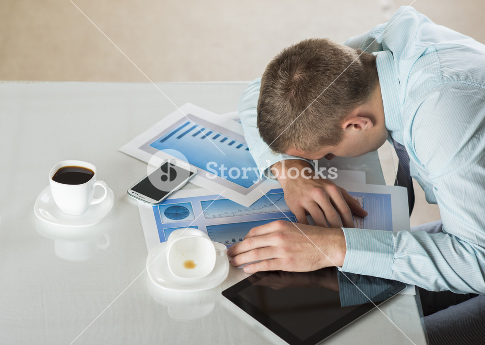 Tired businessman is sleeping in his office