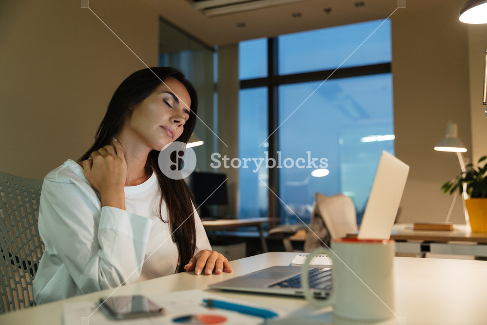 Tired fatigued young businesswoman sitting and working in office