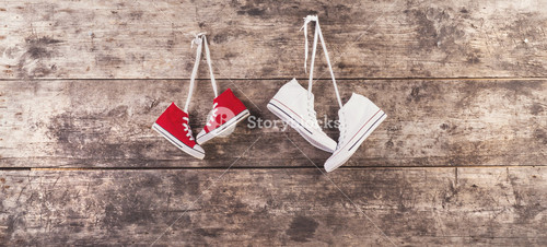 Two pairs of sneakers hang on a nail on a wooden fence background