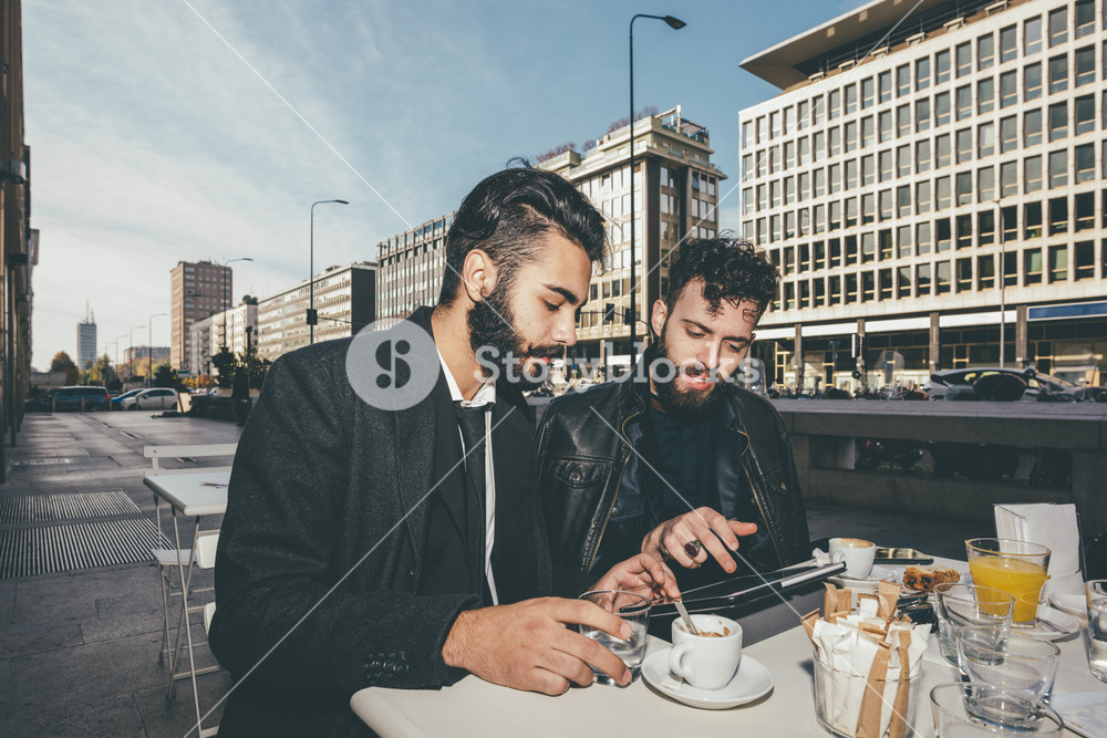 Two young bearded caucasian modern business man sitting in a bar, having breakfast, looking down the screen of a tablet - business, work, technology concept - shot with flash