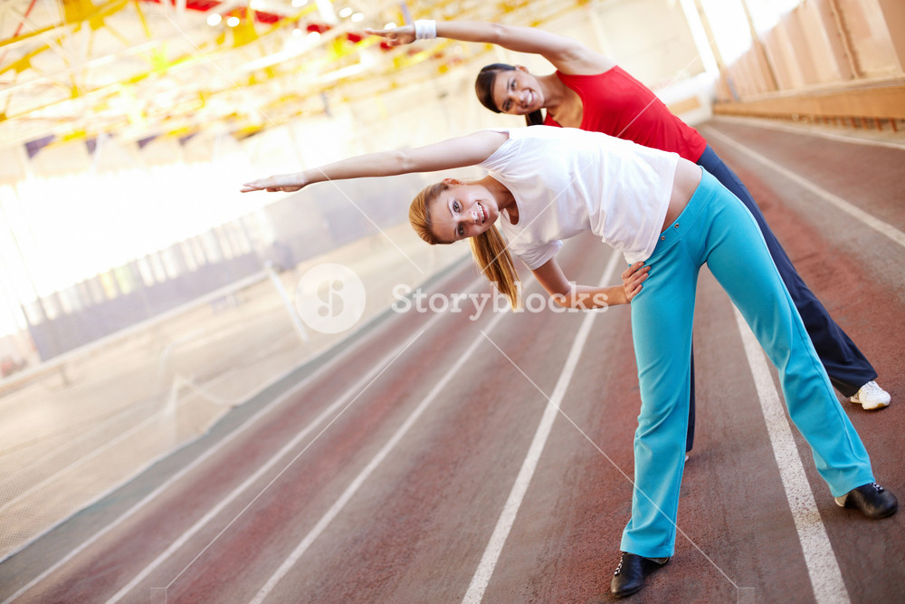 Two young girls making exercises synchronously