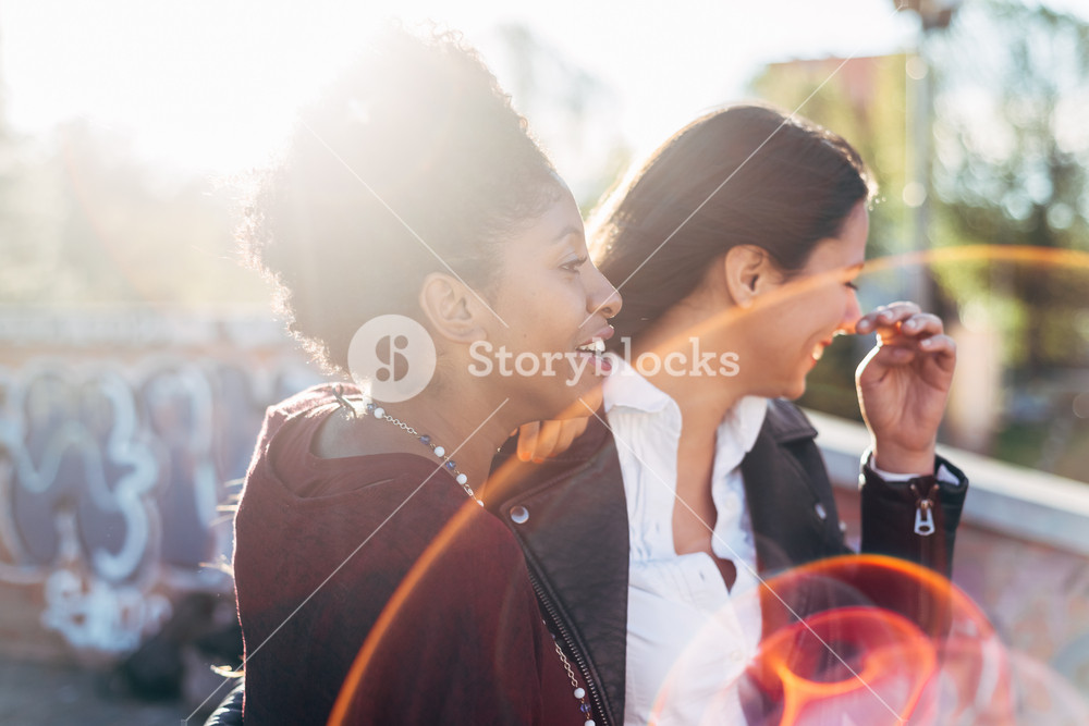Two young women friends having fun together outdoor in city back light - friendship, interaction, happiness concept