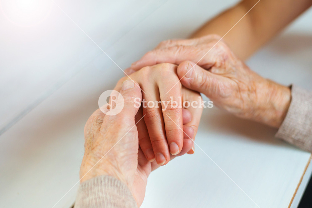 Unrecognizable grandmother and her granddaughter holding hands.