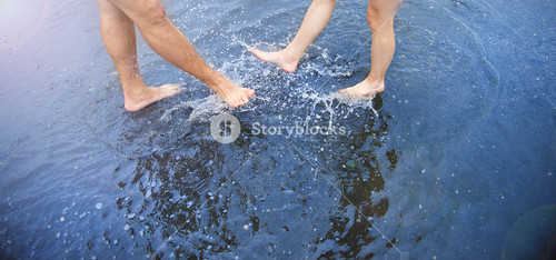 Unrecognizable woman and man walking barefoot through a puddle