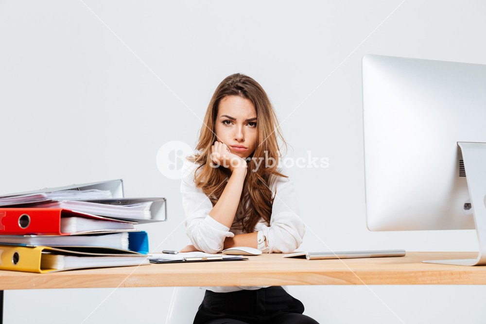 Upset sad businesswoman sitting at her working place over white background