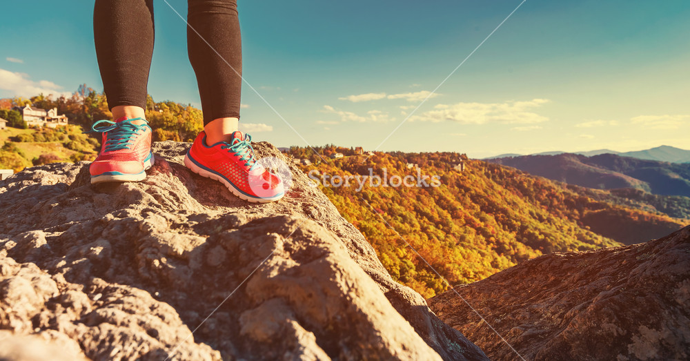 Woman standing at the edge of a cliff high above the mountains