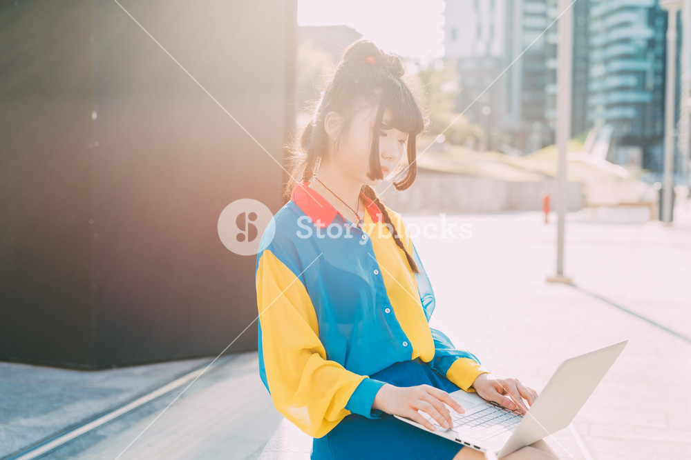 young beautiful asian millennial woman nonconformist outdoor in city back light using computer tapping the keyboard - student, technology, social network concept