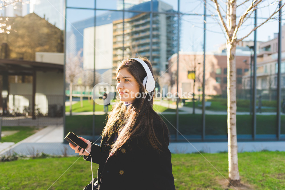 Young beautiful eastern woman outdoor in the city listening music with head phones and smart phone hand hold - music, relaxing, technology concept