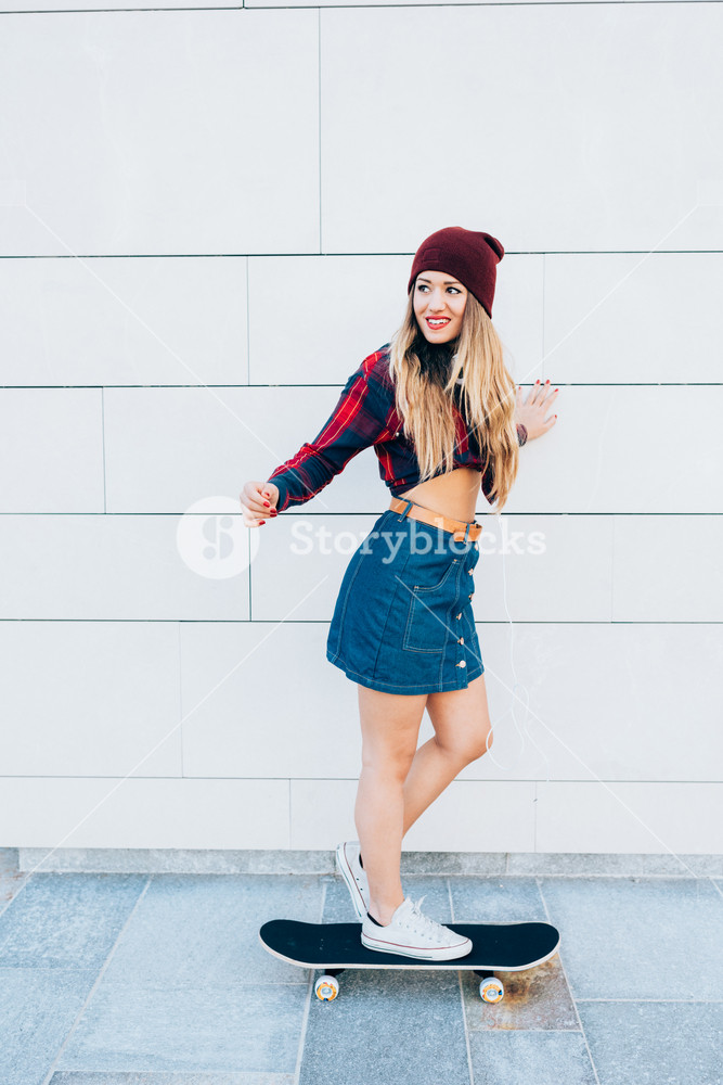 Young blonde caucasian woman riding skateboard outdoor in the city - sportive, happiness, rebel concept