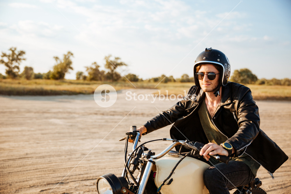 Young brutal man in a black jacket and glasses driving retro motorcycle