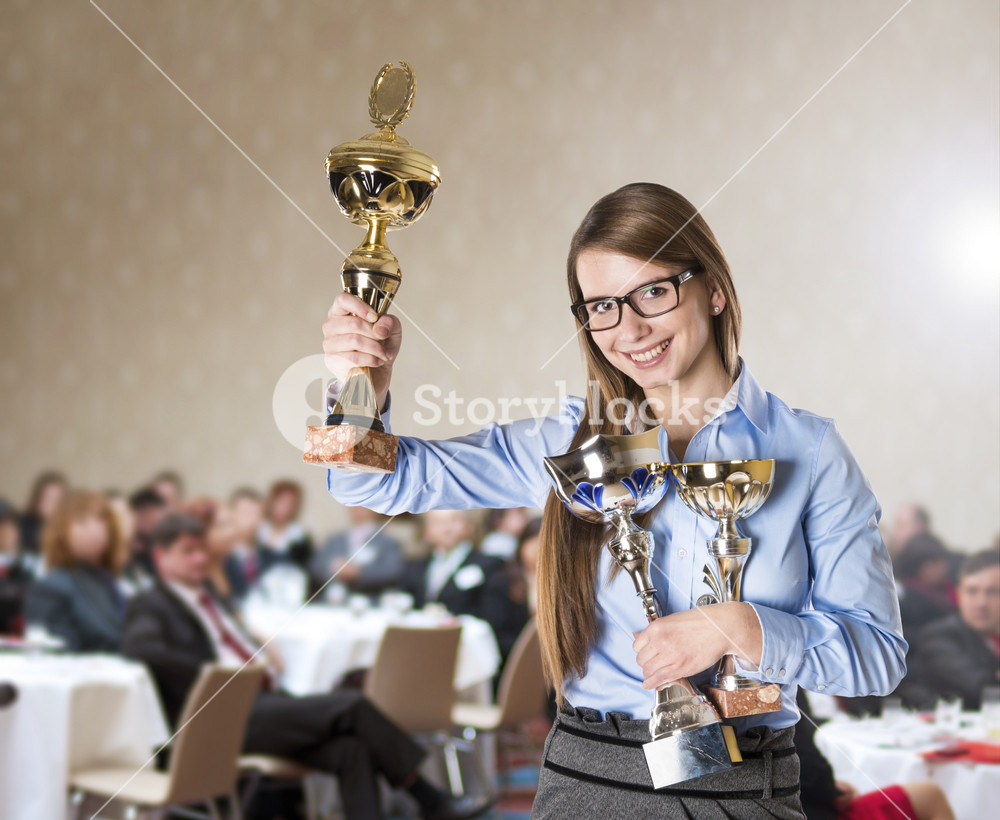 Young business woman was awarded on corporate conference.