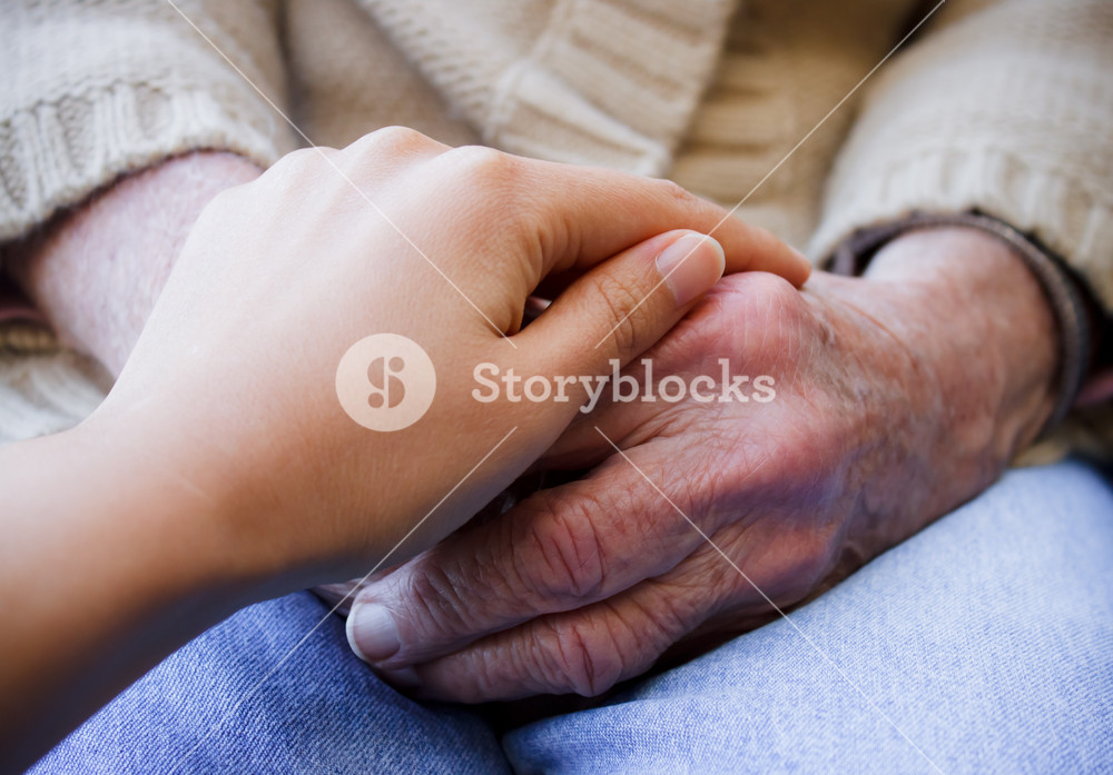 Young caregiver holding hands with senior lady
