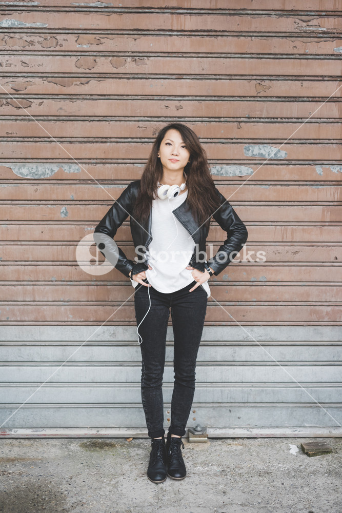 young handsome asiatic chinese woman posing leaning against a rolling shutter, hands in pocket and headphone around her neck, looking in camera serious - thinking future, thoughtful concept
