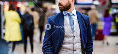 Young handsome businessman standing at the crowded station