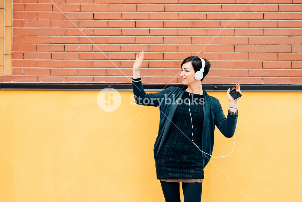 Young handsome caucasian brown hair woman leaning against a wall, listening music with headphones and smart phone hand hold, dancing - serene, enjoying, music concept