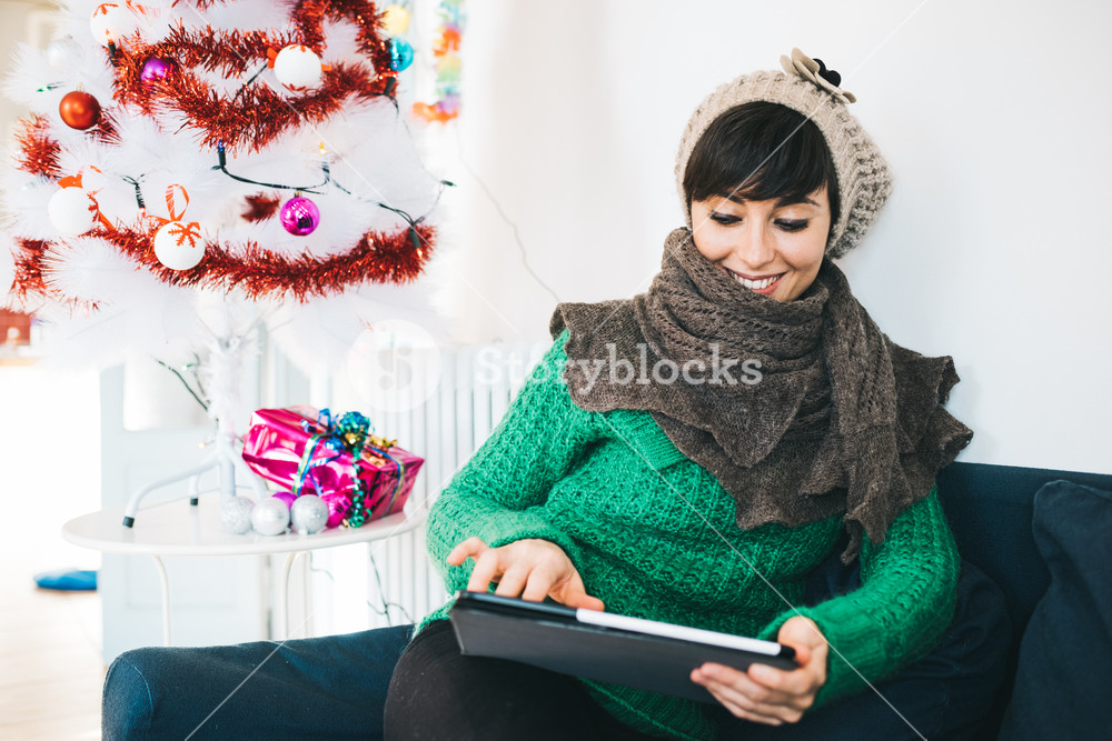 Young handsome caucasian brown hair woman sitting on sofa, holding tablet looking downward and tapping the screen, smiling - christmas, technology, social network, communication concept