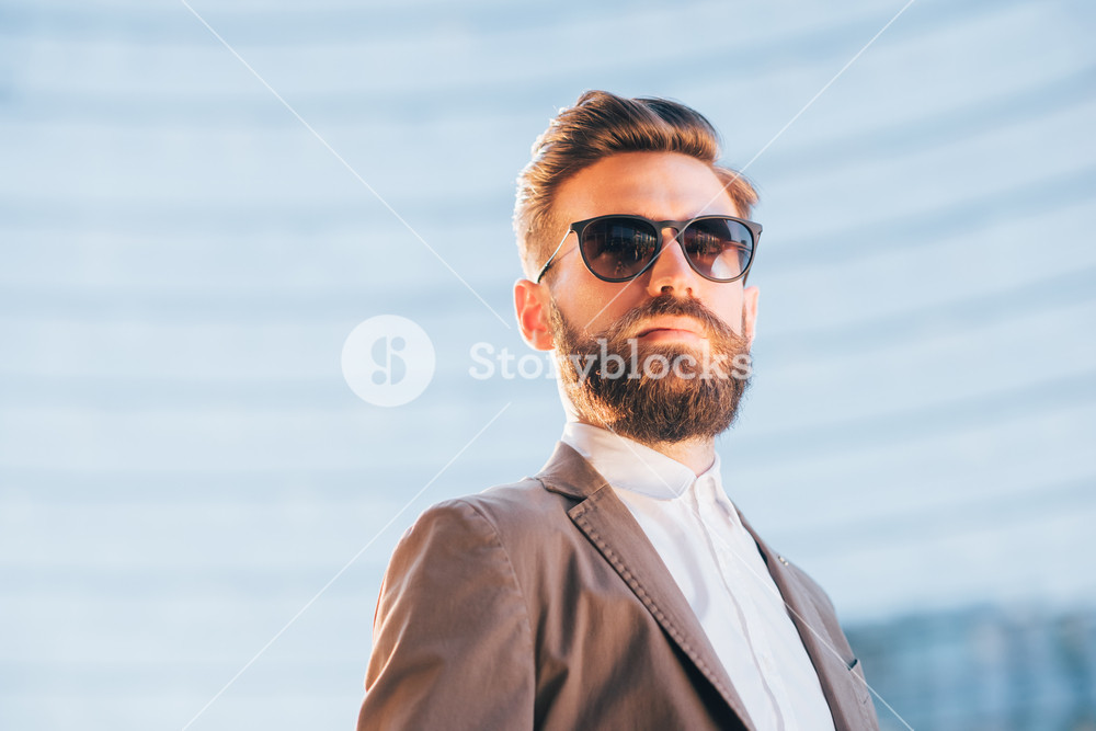 Young handsome modern businessman posing leaning against a wall, overlooking left, wearing a coat - business, success concept