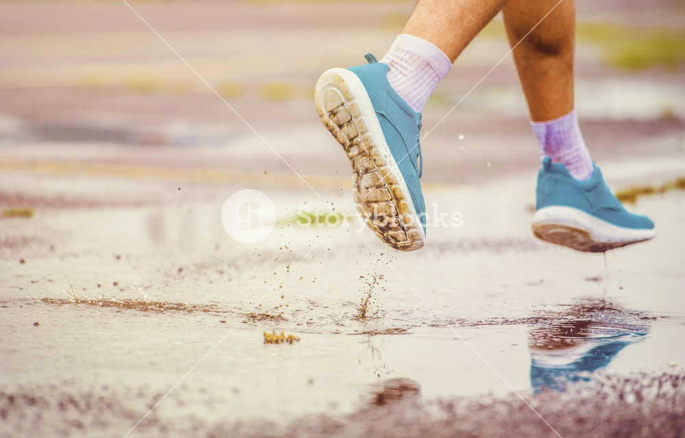 Young man jogging on asphalt in rainy weather