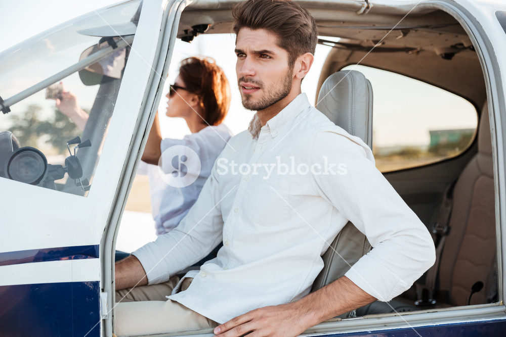 Young pilot and beautiful stewardess sitting together inside airplane cabin
